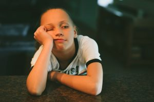 Bored generation Y child tween girl sitting without technology mobile device with nothing to do