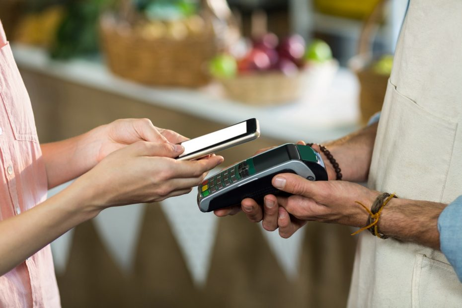Woman making a payment by using NFC technology